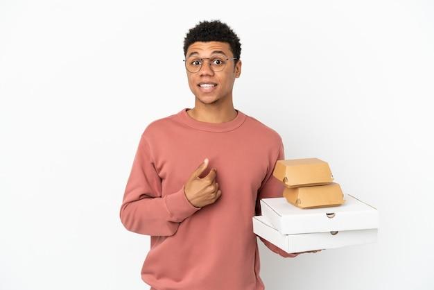 Junger afroamerikanischer mann, der einen burger und pizzas isoliert auf weißem hintergrund mit überraschendem gesichtsausdruck hält