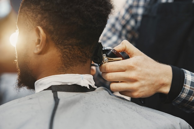 Junger afroamerikanischer mann, der friseursalon besucht