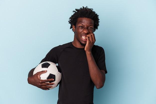 Junger afroamerikanischer mann, der fußball spielt, isoliert auf blauem hintergrund, beißt fingernägel, nervös und sehr ängstlich.