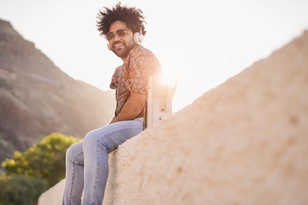 Junger afroamerikanischer mann, der im freien sitzt und bei sonnenuntergang musik von der vintage-boombox-stereoanlage hört?
