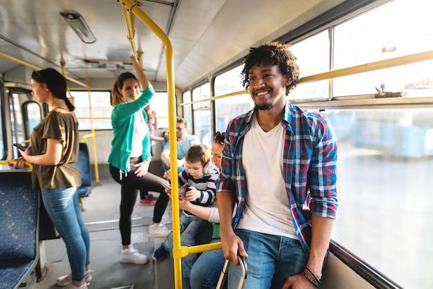 Junger afroamerikanischer mann, der in einem bus steht und koffer hält. im hintergrund sitzen und stehen menschen.