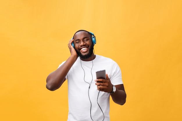 Junger afroamerikanischer mann, der kopfhörer trägt und musik genießt
