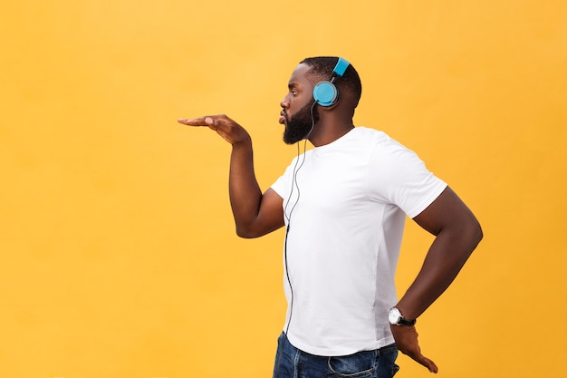 Junger afroamerikanischer mann, der kopfhörer trägt und musiktanz genießt