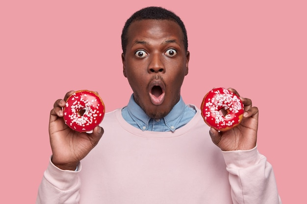 Junger afroamerikanischer mann, der leckere donuts hält