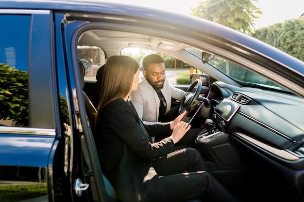 Junger afroamerikanischer mann, der mit weiblichem kaukasischem mitarbeiter während der autofahrt zum geschäftstreffen kommuniziert
