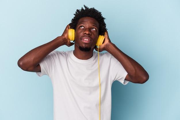 Junger afroamerikanischer mann, der musik einzeln auf blauem hintergrund hört, entspannte sich beim nachdenken über etwas, das einen kopienraum betrachtet.
