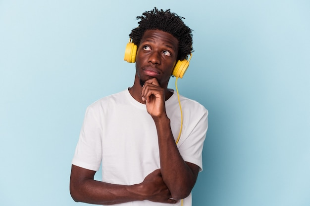 Junger afroamerikanischer mann, der musik hört, einzeln auf blauem hintergrund, der seitlich mit zweifelhaftem und skeptischem ausdruck schaut.