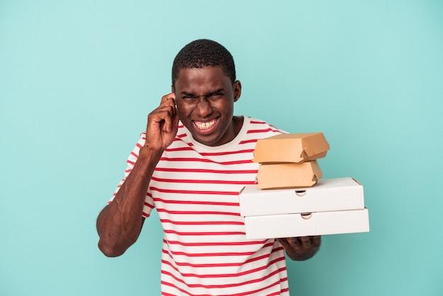 Junger afroamerikanischer mann, der pizzas und burger auf blauem hintergrund isoliert hält und die ohren mit den händen bedeckt.