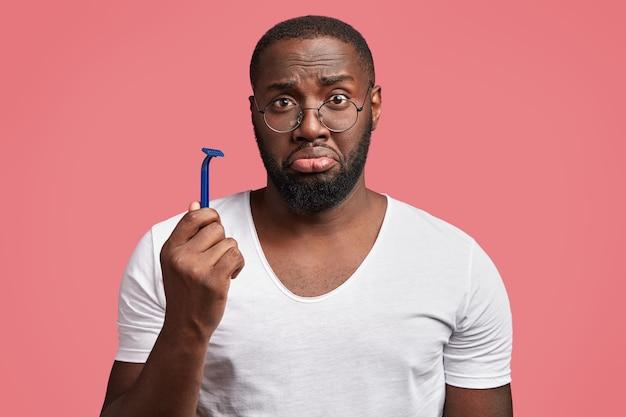 Junger afroamerikanischer mann, der rasiermesser hält
