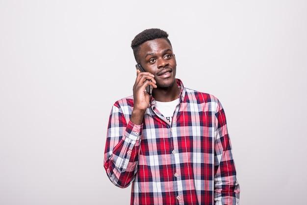 Junger afroamerikanischer mann, der sein telefon lokalisiert auf weiß hält