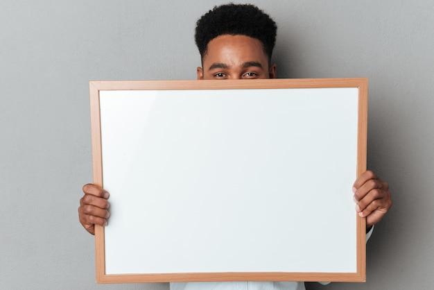 Junger afroamerikanischer mann, der sich hinter leerem brett versteckt