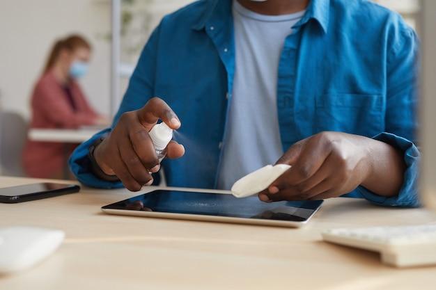 Junger afroamerikanischer mann, der tablette mit desinfektionstüchern abwischt, während er am schreibtisch im büro nach der pandemie arbeitet