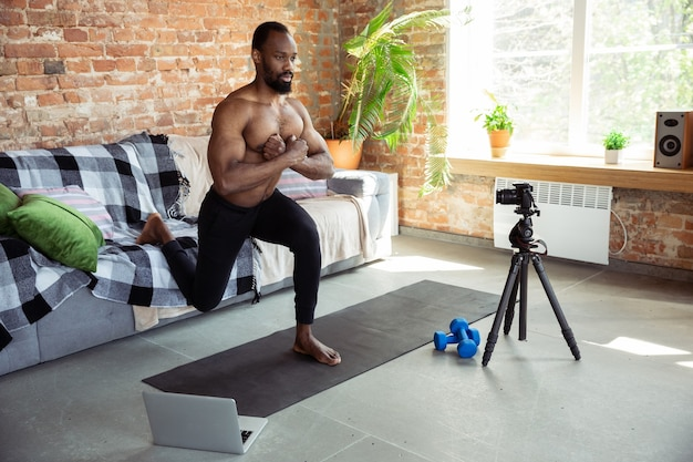 Junger afroamerikanischer mann, der zu hause online-fitnesskurse unterrichtet