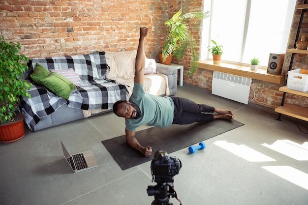 Junger afroamerikanischer mann, der zu hause online-kurse von fitness, aerobic, sportlichem lebensstil während der quarantäne, neuaufnahme vor der kamera, streaming unterrichtet