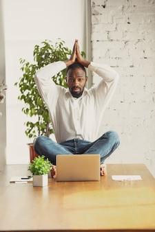 Junger afroamerikanischer mann, der zu hause yoga macht, während er unter quarantäne steht und freiberuflich online arbeitet