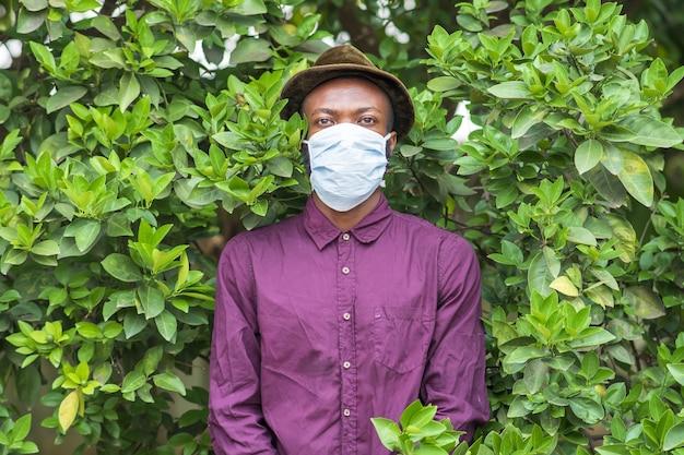 Junger afroamerikanischer mann in einer schützenden gesichtsmaske, die in einem busch steht
