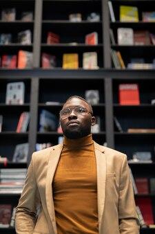 Junger afroamerikanischer mann in eleganter freizeitkleidung, der in einer großen buchhandlung steht?