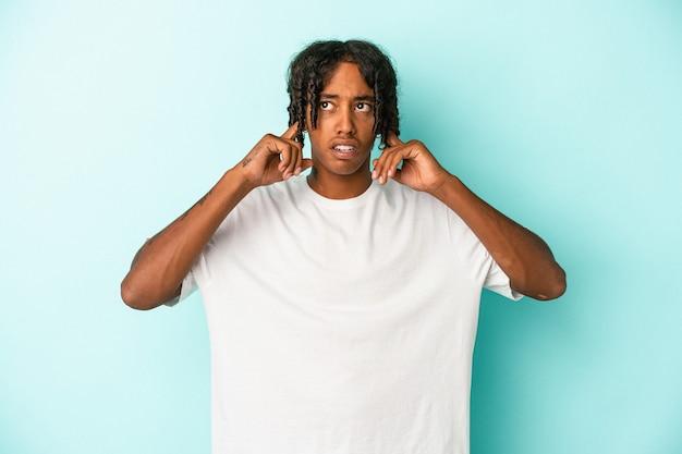 Junger afroamerikanischer mann isoliert auf blauem hintergrund, der die ohren mit den fingern bedeckt, gestresst und verzweifelt durch eine laute umgebung.