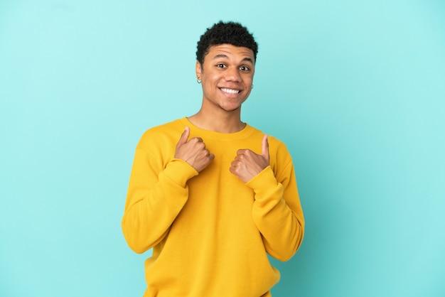 Junger afroamerikanischer mann isoliert auf blauem hintergrund mit überraschtem gesichtsausdruck