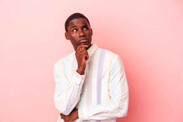 Junger afroamerikanischer mann isoliert auf rosafarbenem hintergrund, der seitlich mit zweifelhaftem und skeptischem ausdruck schaut.