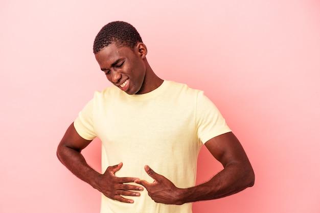 Junger afroamerikanischer mann isoliert auf rosafarbenem hintergrund mit leberschmerzen, bauchschmerzen.