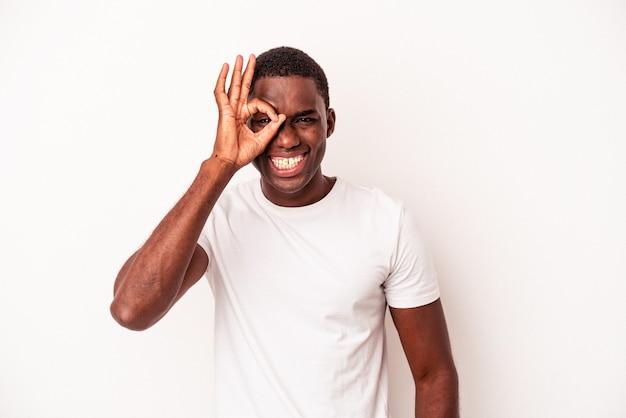 Junger afroamerikanischer mann isoliert auf weißem hintergrund aufgeregt, ok geste auf dem auge zu halten.