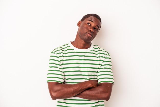 Junger afroamerikanischer mann isoliert auf weißem hintergrund, der davon träumt, ziele und zwecke zu erreichen