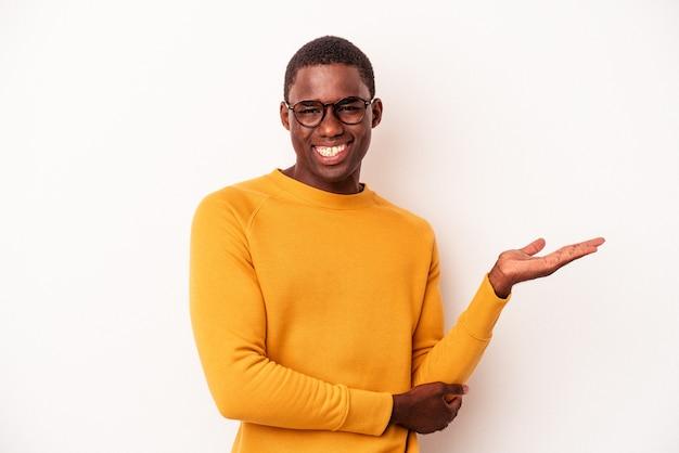 Junger afroamerikanischer mann isoliert auf weißem hintergrund, der einen kopienraum auf einer handfläche zeigt und eine andere hand auf der taille hält.