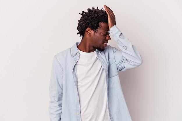 Junger afroamerikanischer mann isoliert auf weißem hintergrund, der etwas vergisst, mit der hand auf die stirn schlägt und die augen schließt.