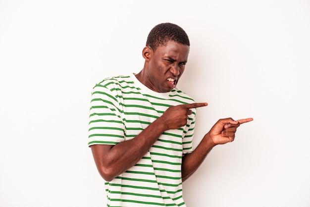 Junger afroamerikanischer mann isoliert auf weißem hintergrund, der mit den zeigefingern auf einen kopienraum zeigt und aufregung und verlangen ausdrückt.