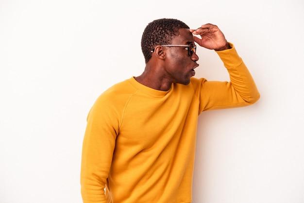 Junger afroamerikanischer mann isoliert auf weißem hintergrund, der weit weg schaut und die hand auf die stirn hält.