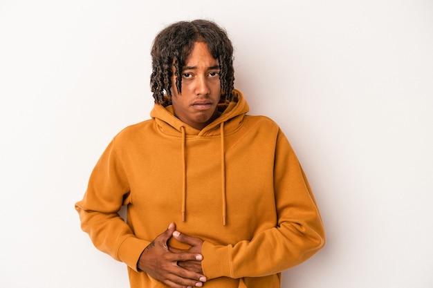 Junger afroamerikanischer mann isoliert auf weißem hintergrund mit leberschmerzen, bauchschmerzen.