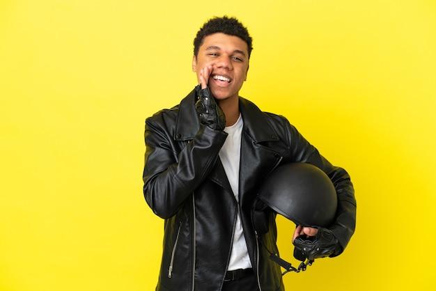 Junger afroamerikanischer mann mit einem motorradhelm auf gelbem hintergrund isoliert, der mit weit geöffnetem mund schreit