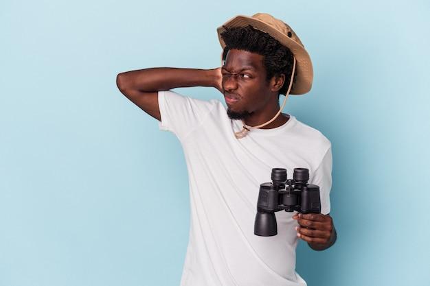Junger afroamerikanischer mann mit fernglas isoliert auf blauem hintergrund, der den hinterkopf berührt, nachdenkt und eine wahl trifft.