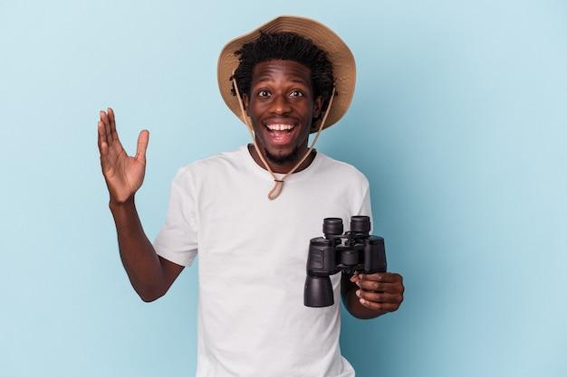 Junger afroamerikanischer mann mit fernglas isoliert auf blauem hintergrund, der eine angenehme überraschung empfängt, aufgeregt und die hände hebt.