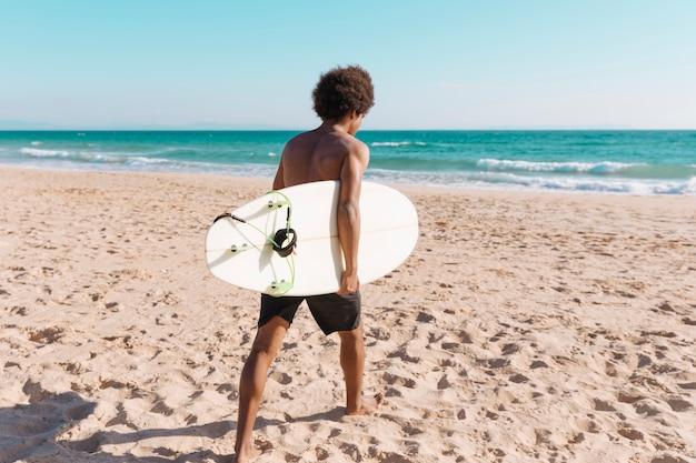 Junger afroamerikanischer mann mit surfbrett am strand