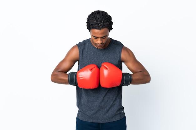 Junger afroamerikanischer mann mit zöpfen auf purpur mit boxhandschuhen