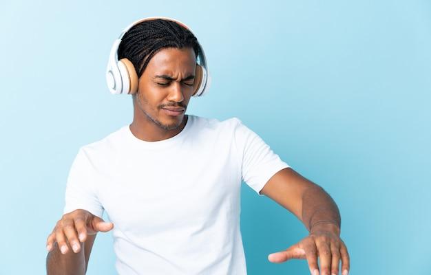 Junger afroamerikanischer mann mit zöpfen lokalisiert auf blauem hintergrund, der musik und tanz hört