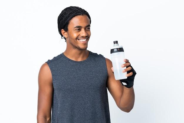Junger afroamerikanischer mann mit zöpfen lokalisiert auf lila hintergrund mit sportwasserflasche
