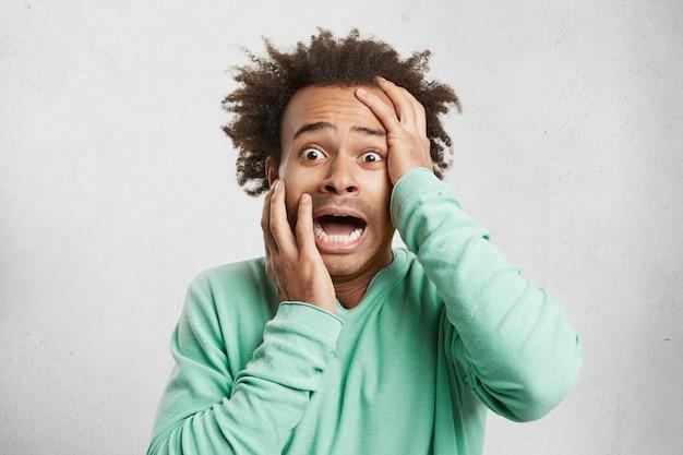 Junger afroamerikanischer mann schreit vor schrecken, hält hände an kopf und mund weit offen