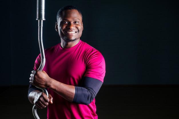 Junger afroamerikanischer mann sportler hockender sportler trainiert hantel t-shirt sportuniformen sportbekleidung schwarzen hintergrund studio gym