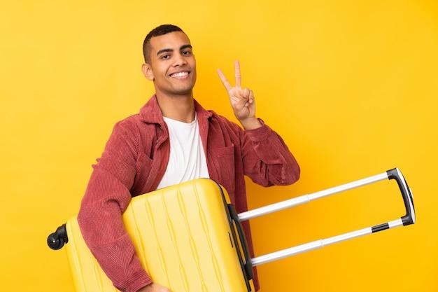 Junger afroamerikanischer mann über isolierter gelber wand im urlaub mit reisekoffer und siegesgeste