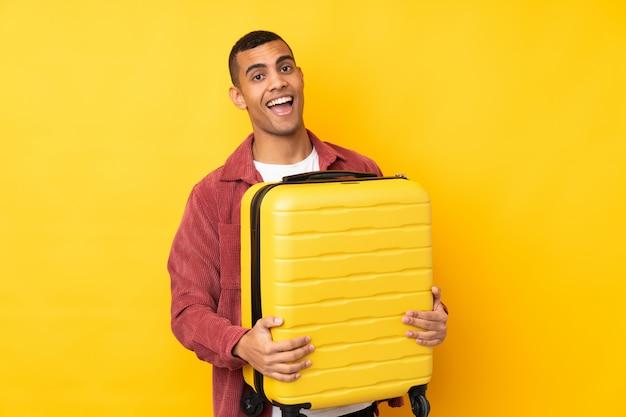 Junger afroamerikanischer mann über isolierter gelber wand im urlaub mit reisekoffer und überrascht
