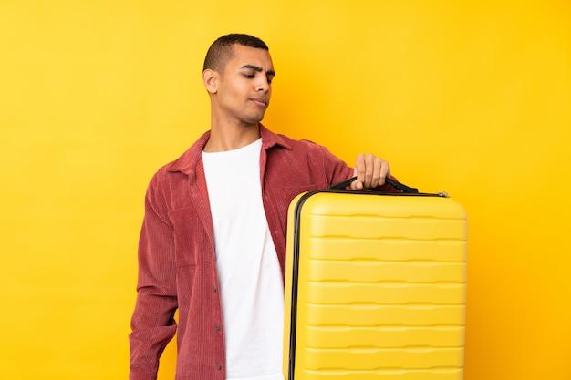 Junger afroamerikanischer mann über isolierter gelber wand im urlaub mit reisekoffer und unglücklich