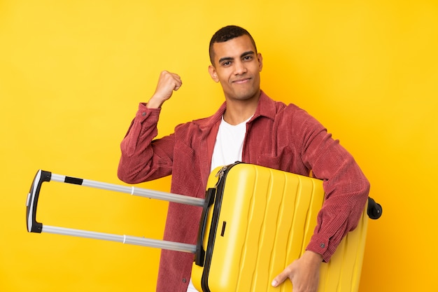 Junger afroamerikanischer mann über isolierter gelber wand im urlaub mit reisekoffer