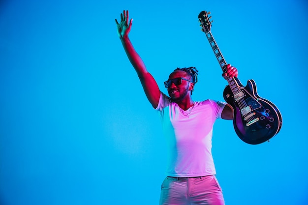 Junger afroamerikanischer musiker, der die gitarre wie ein rockstar auf blauem hintergrund im neonlicht spielt.