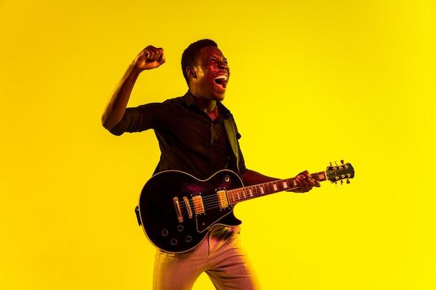 Junger afroamerikanischer musiker, der die gitarre wie ein rockstar auf gelbem hintergrund im neonlicht spielt.