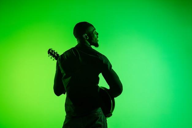 Junger afroamerikanischer musiker, der die gitarre wie ein rockstar auf grün-gelbem hintergrund des farbverlaufs spielt.