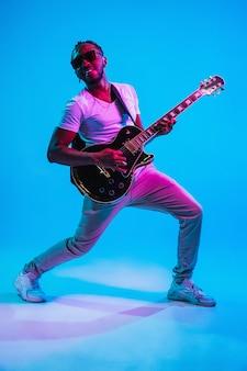 Junger afroamerikanischer musiker, der gitarre wie ein rockstar auf blauem studiohintergrund im neonlicht spielt. konzept der musik, hobby. fröhlicher kerl improvisiert. retro buntes porträt.