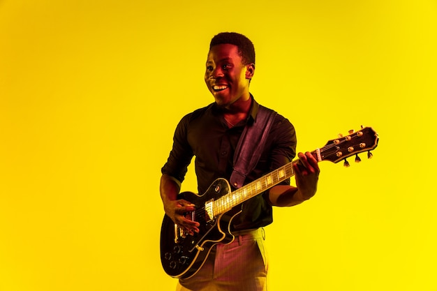 Junger afroamerikanischer musiker, der gitarre wie ein rockstar auf gelbem hintergrund im neonlicht spielt. konzept von musik, hobby, festival, open-air. fröhlicher kerl improvisiert, singt lied.